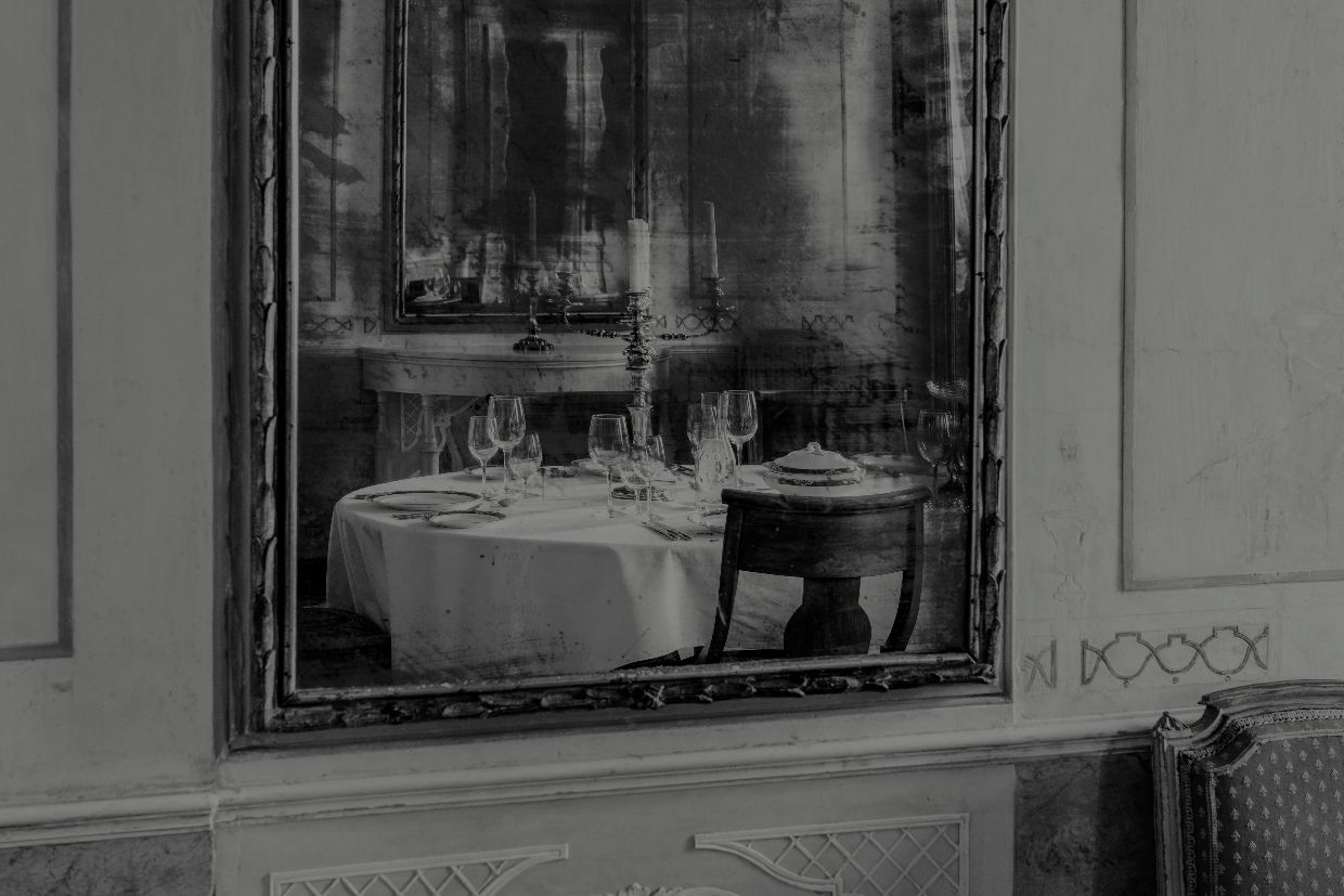 Black and white picture of a palatial room reflected in a mirror in Venice